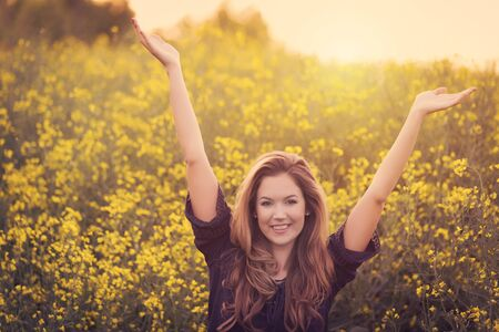 Beauty smiling woman in yellow rapeseed field at sunset