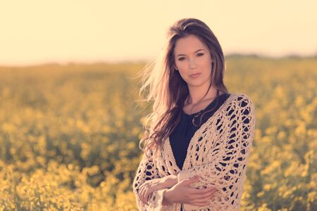 Portrait of beautiful woman in rapeseed field at sunset