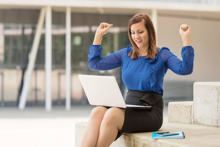 Happy businesswoman using notebook outdoor. Successful woman