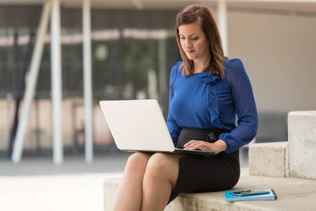 Beauty woman sitting and using a laptop. Outdoor photo