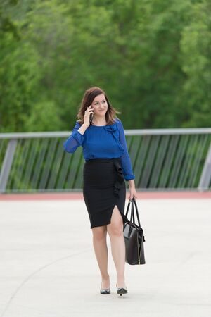 Happy business woman walking and talking on her phone. Outdooe photo