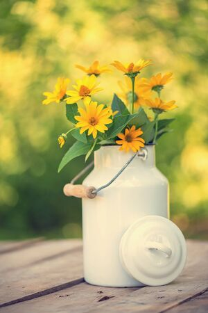 Yellow flower on old wooden table in metal pot