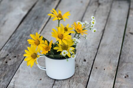 Yellow flower in the cup on the used wooden table Фото со стока