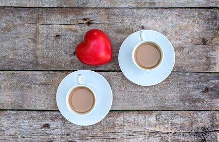 Cup of cappuccino and red heart shape in the wooden table Фото со стока