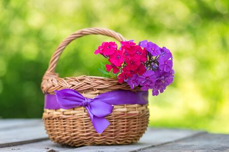 Beauty flowers in basket on a wooden table
