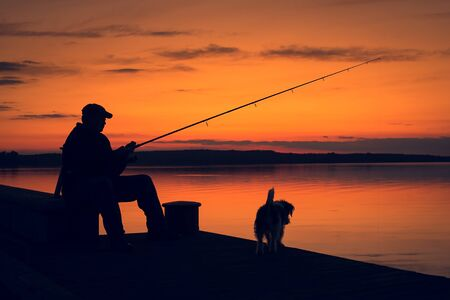 Fisher man fishing in sunset. Silhouette photo of a fisher man