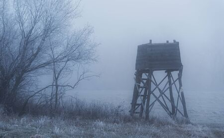 Hunting tower on the edge of the forest a foggy day