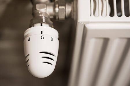 Closeup photo of a heating radiator with temperature regulator