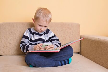 Smartphone or a book. Young kid choose the phone. Technology and communication concept  免版税图像