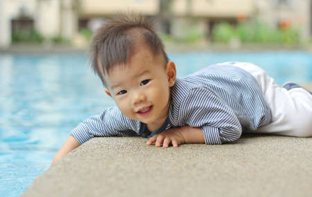 lying on side: Asian child by the pool