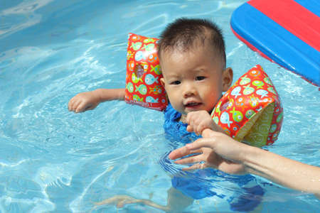 Asian baby guided in pool