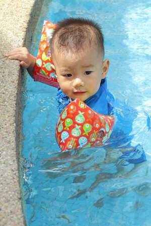 Asian baby at pool edge