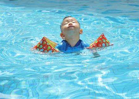 Asian baby floating in pool photo