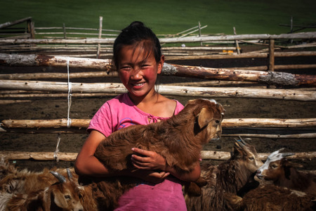 mongols: A nomadic mongolian girl with a little baby goat Editorial