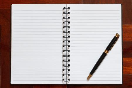 papel de notas: Notebook and pen. Blank white page. Wooden floor in the background. Foto de archivo