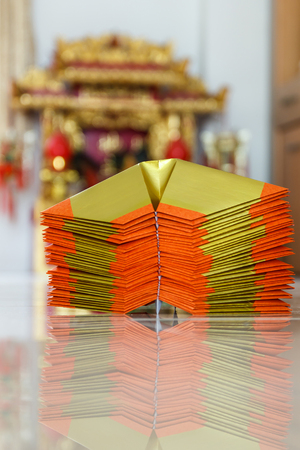 tabernacle: Chinese paper art use for worship.And a shrine in the background.Focus on the top paper. Stock Photo