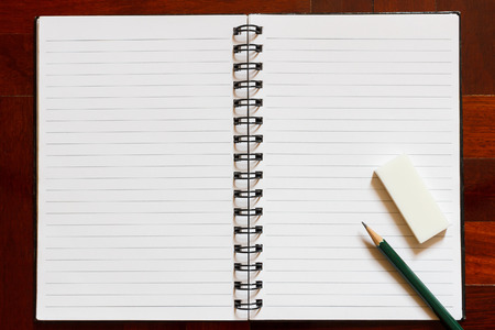 blank page: Open notebook with blank page and pencil and eraser. Wooden floor in the background.
