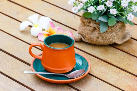 morning breakfast: Hot coffee and Plumeria and flowers on the wooden table.Focus on the cup. Stock Photo