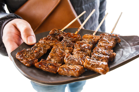 hida: Isolated man holding beef bbq in a plate.With clipping path.