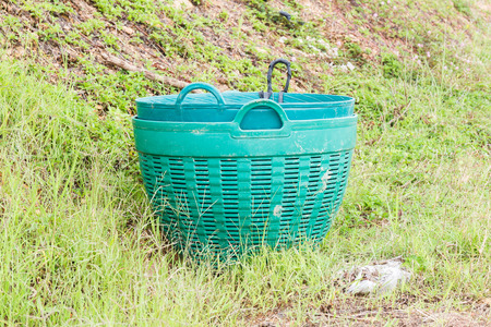 cesto basura: cesta de basura de plástico verde en el jardín.