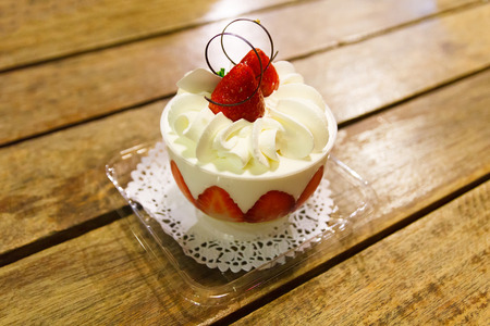 Strawberry cup cake on wooden table.