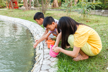 children pond: Young Thai children feeding fish in pond. Stock Photo