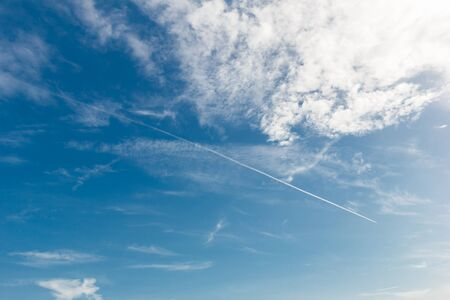 contrail: Blue sky with cloud and contrail.