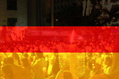 Germany flag with people praying in background.