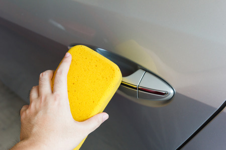 Hand cleaning cars dirt with yellow sponge.