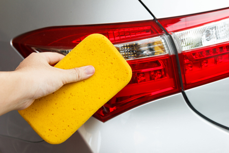valet: Hand cleaning cars dirt with yellow sponge.