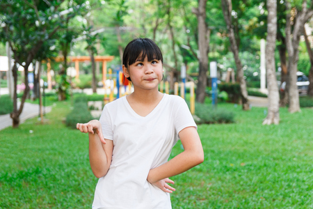 Asian girl thumb down with playground in background.