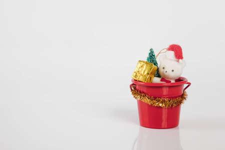 Teddybear sitting in a bucket with a christmas present photo