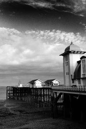 Pier under dramatic sky on water front photo