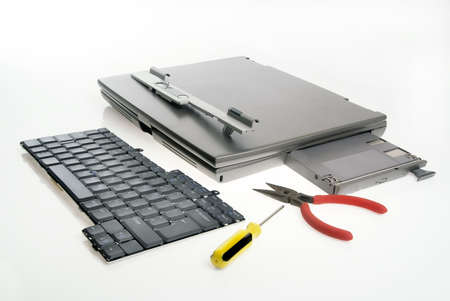 upgrading: Laptop components and tools against white Stock Photo