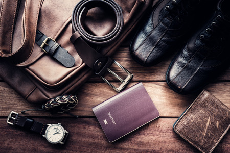 Still life with Mens casual outfits with leather accessories on brown wooden background, beauty and fashion, travel concept