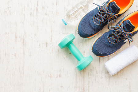 Blue running shoes with fitness accessories on white wooden background Standard-Bild