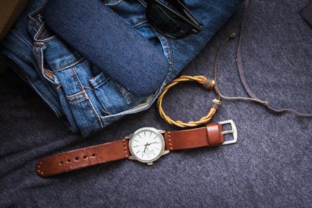 Das Zubehör der Männer mit Blue Jeans, Uhr und Sonnenbrille auf grauem T-Shirt Hintergrund Standard-Bild - 86363824