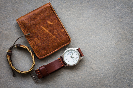 Men's accessories with brown leather wallet and watch on gray background