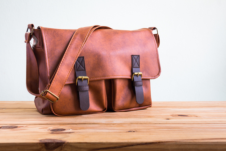 Men's fashion with brown leather bag on wooden table over wall background