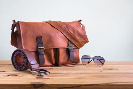 Mens accessories with brown leather bags, belt and sunglasses on wooden table over wall background Stock fotó