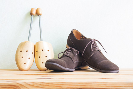 Men's accessories, vintage shoes and wooden shoe tree on wooden table over white wall background Standard-Bild