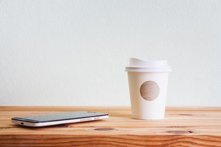 Tasse Kaffee und intelligentes Telefon auf Holztisch über weißem Wandhintergrund Standard-Bild - 86937154