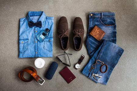 Die zufällige Kleidung der Männer kleidet mit Jeans, Lederschuhen und Zusätzen auf grauem Hintergrund Standard-Bild - 87066829