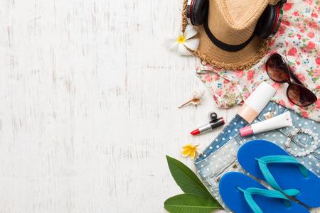 Beiläufige Sommerkleidung der Frauen mit Zubehöreinzelteilen auf weißem rustikalem hölzernem Bretthintergrund, obenliegende Draufsicht, flay legen Standard-Bild - 86585888