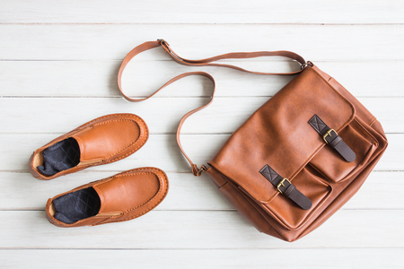 Fashionable concept, men's casual outfits with leather accessories, brown shoes and bag on white wooden board background