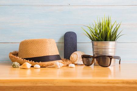 Das Zubehör der Männer mit braunem Hut, gefälschtem Baum und Sonnenbrille auf Holztisch über blauem rustikalem Bretthintergrund, Sommerkonzept Standard-Bild - 86689094