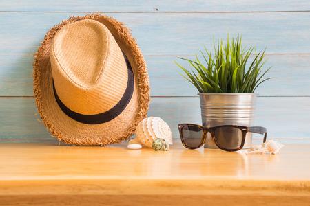 Das Zubehör der Männer mit braunem Hut, Sonnenbrille und Fälschungsbaum auf Holztisch über blauem rustikalem Bretthintergrund, Sommerkonzept Standard-Bild - 86689095