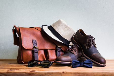Men's accessories with brown leather bag, brown shoes, classic hat, sunglasses and blue bow tie on wooden table over wall background Standard-Bild