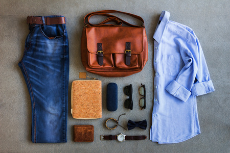 Flat lay of men's casual outfits with accessories on gray background Standard-Bild
