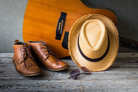 Still life with boots, hat, sunglasses and guitar on wooden table over grunge background Standard-Bild